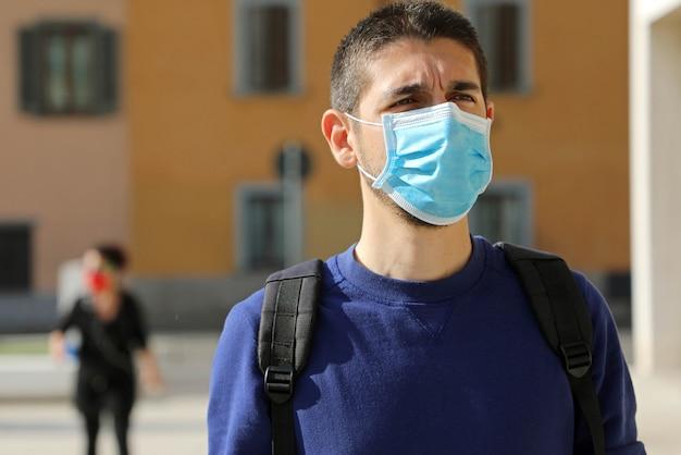 Porträt des mannes mit maske geht unter berücksichtigung der sozialen distanzierung während der pandemie-coronavirus-krankheit 2019.