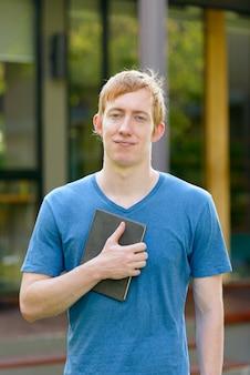 Porträt des mannes mit roten haaren im garten im freien