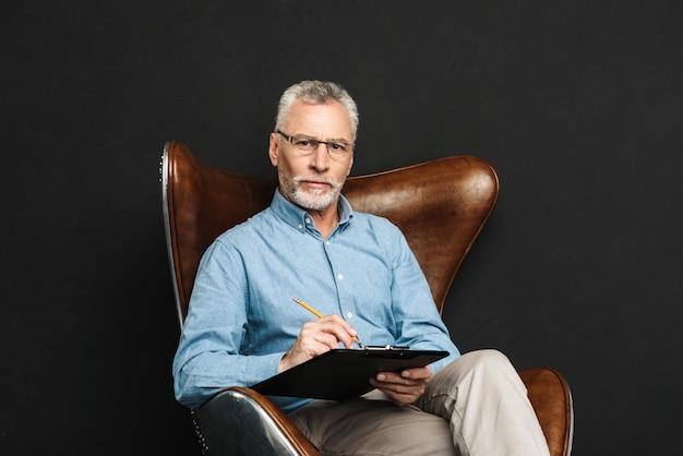 Porträt des mannes mittleren alters 60s mit grauem haar und bart, der auf hölzernem sessel sitzt und klemmbrett mit dokumenten hält, lokalisiert über schwarzer wand