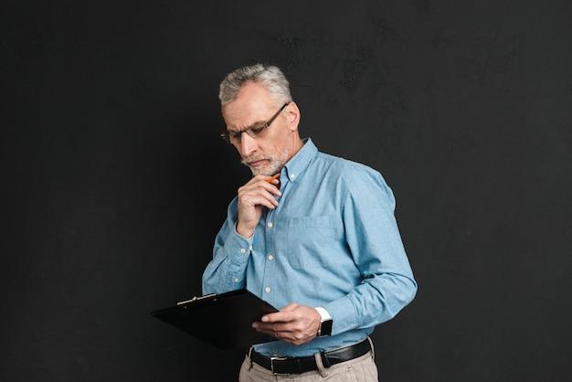 Porträt des mannes mittleren alters 60s mit grauem haar und bart, der mit dokumenten arbeitet, während zwischenablage hält, lokalisiert über schwarzer wand
