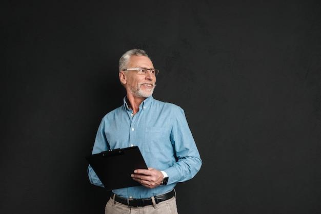 Porträt des mannes mittleren alters 60s mit grauem haar und bart, der nach oben beiseite schaut, zwischenablage mit dokumenten haltend, lokalisiert über schwarzer wand