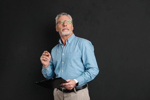 Porträt des mannes mittleren alters 60s mit grauem haar und bart, der nach oben schaut, während zwischenablage mit dokumenten hält, lokalisiert über schwarzer wand