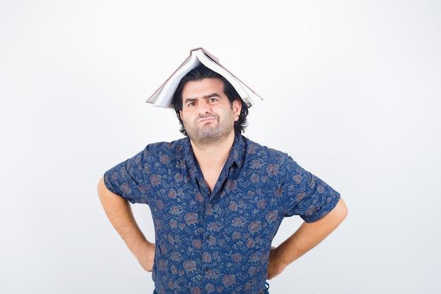 Porträt des mannes mittleren alters, der buch auf kopf als hausdach im hemd hält und zögernde vorderansicht schaut