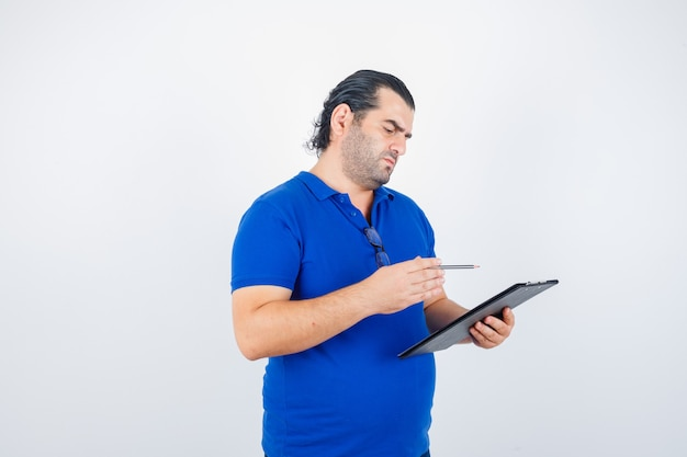 Porträt des mannes mittleren alters, der durch zwischenablage schaut, während bleistift im polo-t-shirt hält und nachdenkliche vorderansicht schaut
