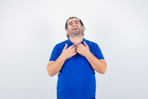 Porträt des mannes mittleren alters, der hände auf brust in polo-t-shirt hält und fröhliche vorderansicht schaut