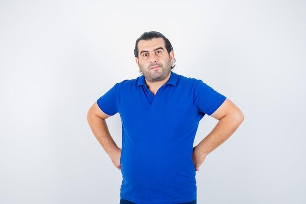 Porträt des mannes mittleren alters, der hände auf hüfte im blauen t-shirt hält und selbstbewusste vorderansicht schaut