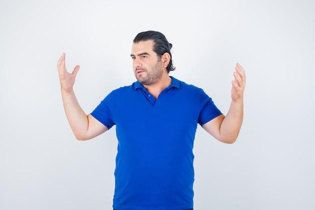 Porträt des mannes mittleren alters, der hände im blauen t-shirt erhebt und nachdenkliche vorderansicht schaut