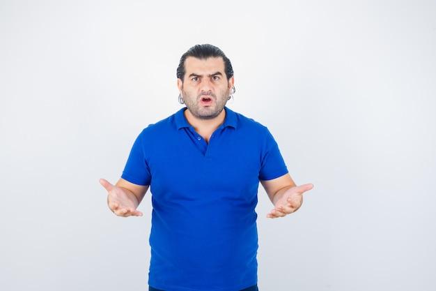 Porträt des mannes mittleren alters, der hände in der aggressiven weise im blauen t-shirt hält und gestresste vorderansicht schaut
