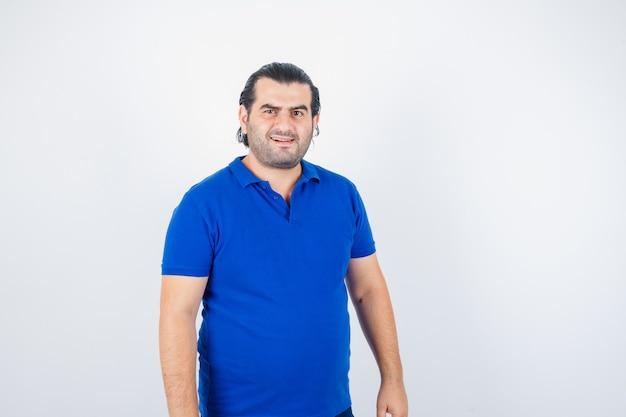 Porträt des mannes mittleren alters, der kamera im blauen t-shirt betrachtet und ernsthafte vorderansicht schaut