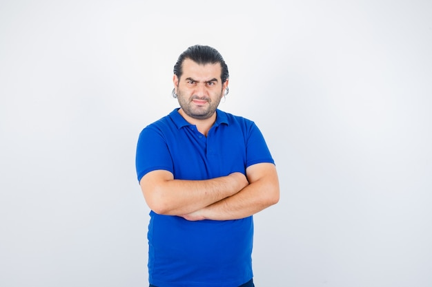 Porträt des mannes mittleren alters, der mit verschränkten armen im blauen t-shirt steht und selbstbewusste vorderansicht schaut