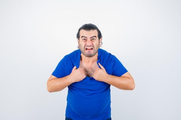 Porträt des mannes mittleren alters, der sein t-shirt im blauen t-shirt zerreißt und wütende vorderansicht schaut