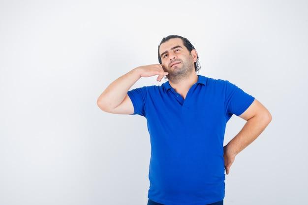 Porträt des mannes mittleren alters, der telefongeste im polo-t-shirt zeigt und nachdenkliche vorderansicht schaut