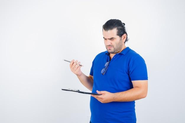 Porträt des mannes mittleren alters, der zwischenablage betrachtet, während bleistift im polot-shirt hält und nachdenkliche vorderansicht schaut