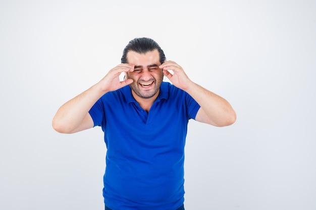 Porträt des mannes mittleren alters lachend, während händchenhalten auf kopf im blauen t-shirt und fröhliche vorderansicht schauend
