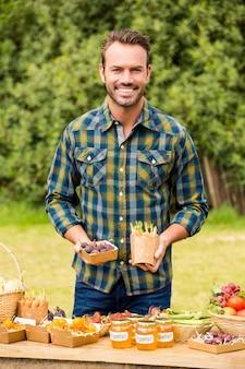 Porträt des mannes organisches gemüse verkaufend
