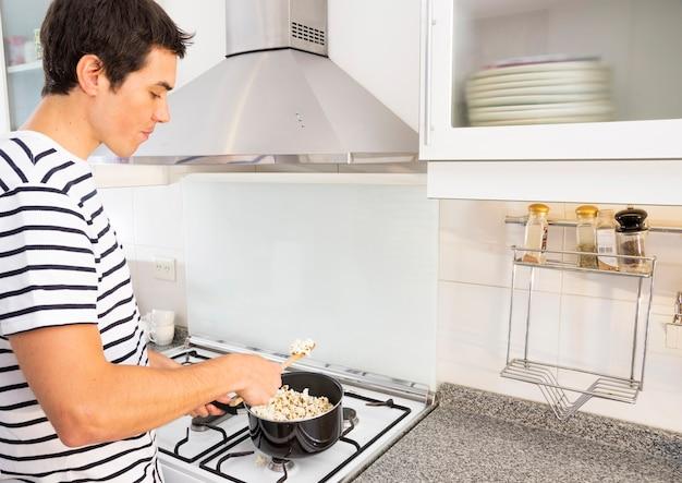 Porträt des mannes popcorn in der soßenwanne in der küche braten