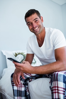 Porträt des mannes sitzend auf bett und eine textnachricht am telefon schreibend