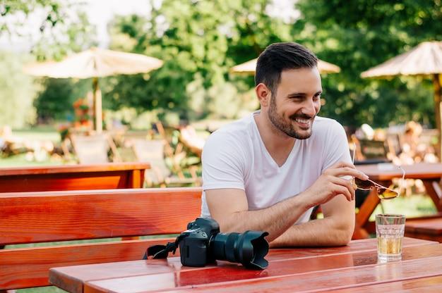 Porträt des mannes sitzend im café, sonnenbrille halten
