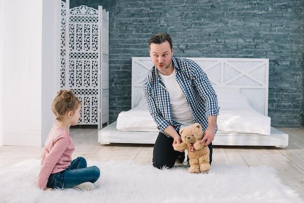 Porträt des mannes spielend mit tochter im schlafzimmer