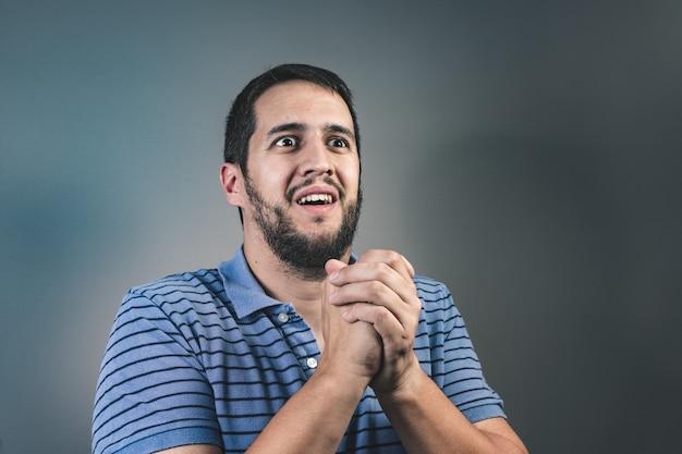 Porträt des mannes umklammerte hände zeigen und um hilfe oder entschuldigung bitten. bitte vergib mir das konzept