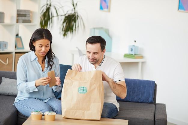 Porträt des mannes und der frau, die nahrungsmittellieferbeutel öffnen, während mittagessen zum mitnehmen im büro genießen