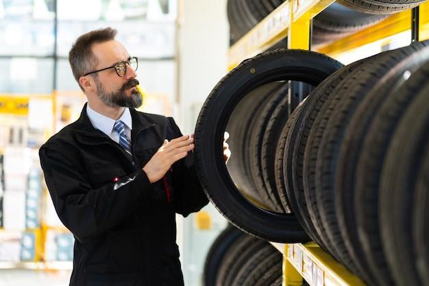 Porträt des mechanikermannes mit autoreifen an der tankstelle. männlicher mechaniker, der autoreifen im autogeschäftsshop hält