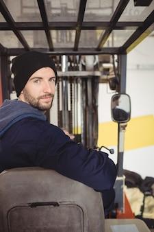Porträt des mechanikers, der auf gabelstapler sitzt