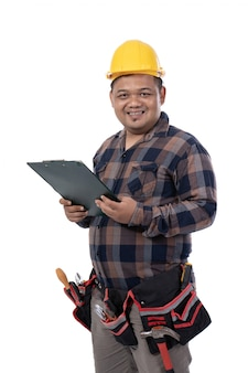 Porträt des mechanikers, der helm hält, der eine zwischenablage hält