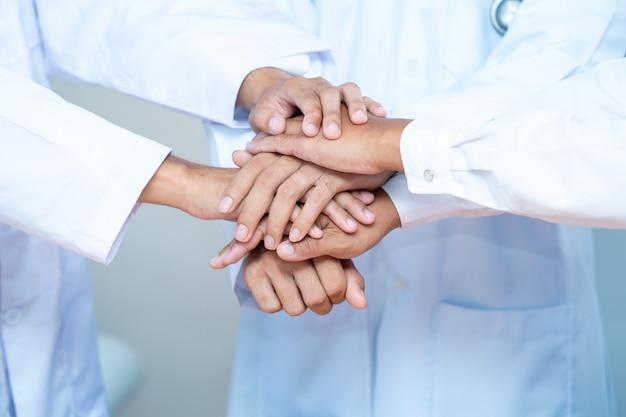 Porträt des medizinischen teams, das hände in einem symbol der einheit zusammenstapelt.