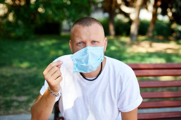 Porträt des menschen nimmt schutzmaske im park im freien in der stadt ab, konzept selbstpflege, leben während der coronavirus-pandemie, über quarantäne, stop covid-19, kehren zum normalen leben zurück.