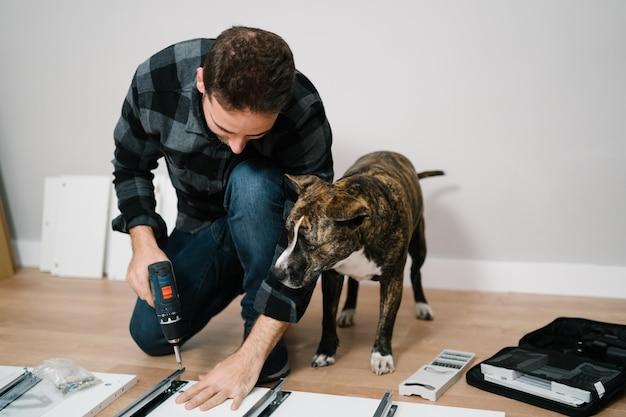 Porträt des menschen und seines hundes, die möbel zusammenbauen. machen sie es sich selbst möbelmontage.