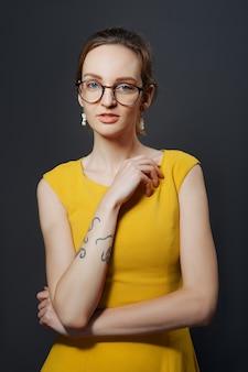 Porträt des misstrauischen mädchens mit tätowierung auf ihrem arm.