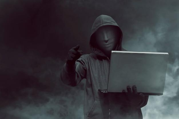 Porträt des mit kapuze hackers mit der maske, die laptop bei der stellung hält