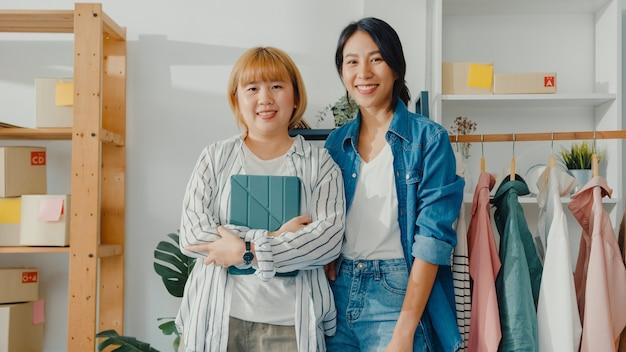 Porträt des modedesigners der jungen asiatischen frauen mit glücklichem lächeln, verschränkten armen und blick nach vorne beim arbeiten des bekleidungsgeschäfts im heimbüro