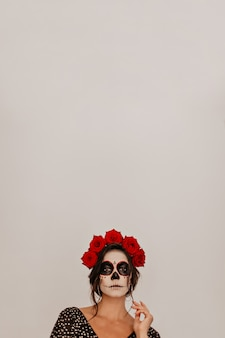 Porträt des modells gegen weiße wand, die in der krone der natürlichen blumen aufwirft. halloween skelett make-up sieht ungewöhnlich aus