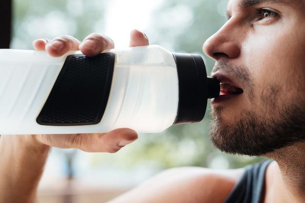 Porträt des modells im fitnessstudio mit flasche hautnah