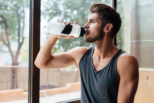 Porträt des modells im fitnessstudio mit flasche with