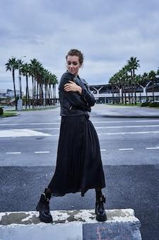 Porträt des modemädchens mädchen in der schwarzen kleidung kreuzt die stadtstraße