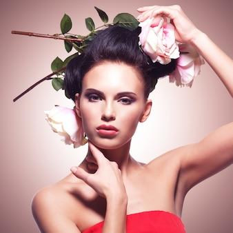 Porträt des modemodells mit blumenrosen in den haaren. instagram-styling