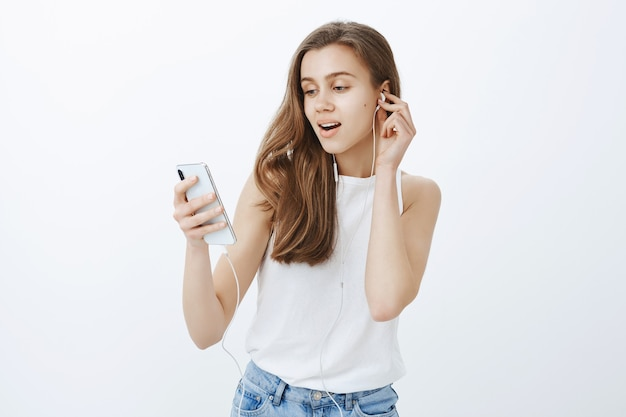 Porträt des modernen attraktiven mädchens legte kopfhörer, hörenden podcast oder musik auf handy