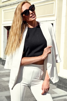 Porträt des modernen geschäftsfrauenmodells der sexy mode im weißen anzug, der auf dem straßenhintergrund aufwirft