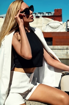Porträt des modernen geschäftsfrauenmodells der sexy mode im weißen anzug mit handtasche, die auf dem straßenhintergrund hinter blauem himmel aufwirft