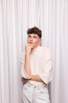 Porträt des modernen jungen vor weißem vorhang
