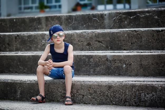 Porträt des modernen kleinen jungen in der sonnenbrille und in der kappe, die auf steinschritte stationieren. kindheit. sommer.