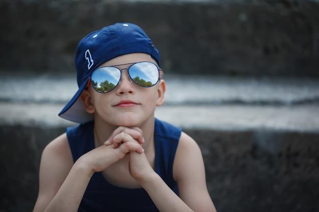 Porträt des modernen kleinen jungen in der sonnenbrille und in der kappe. kindheit. sommer.
