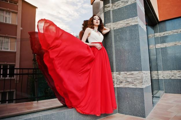 Porträt des modernen mädchens am roten abendkleid warf hintergrundspiegelfenster des modernen gebäudes auf. kleid in die luft blasen