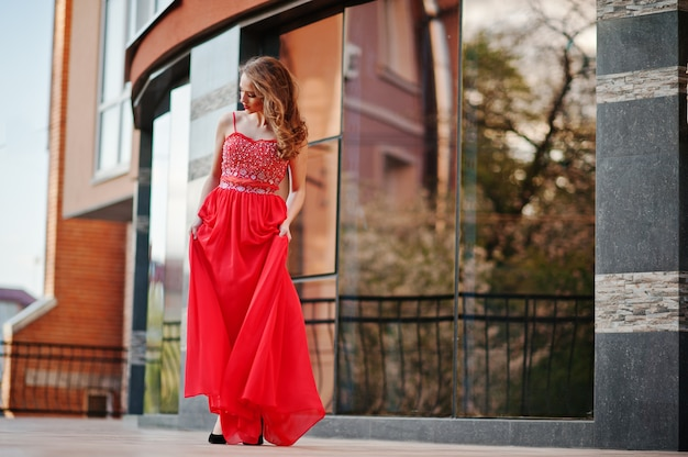 Porträt des modernen mädchens am roten abendkleid warf hintergrundspiegelfenster des modernen gebäudes auf