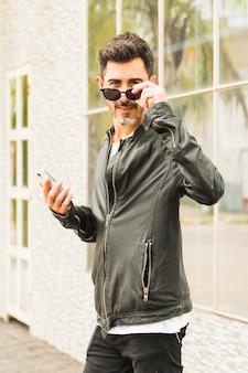 Porträt des modernen mannes die schwarze sonnenbrille tragend, die in der hand das intelligente telefon betrachtet kamera hält