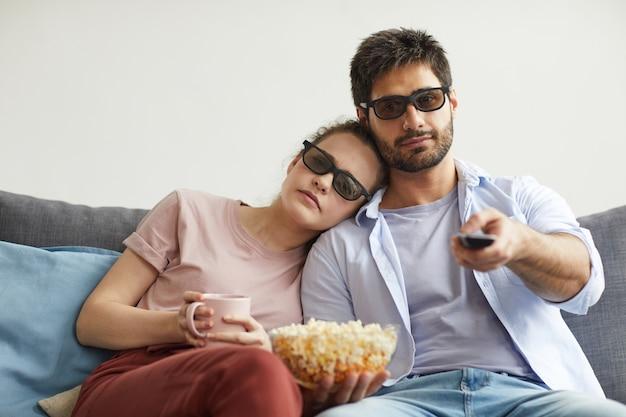 Porträt des modernen paares, das zusammen fernsieht, während es auf sofa sitzt und zu hause eine stereobrille trägt und faule zeit genießt