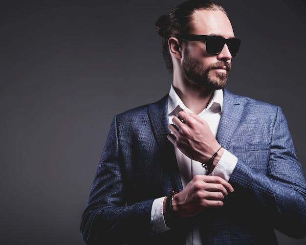 Porträt des modischen hipster-geschäftsmannmodells der schönen mode, gekleidet im eleganten blauen anzug, der auf grau aufwirft
